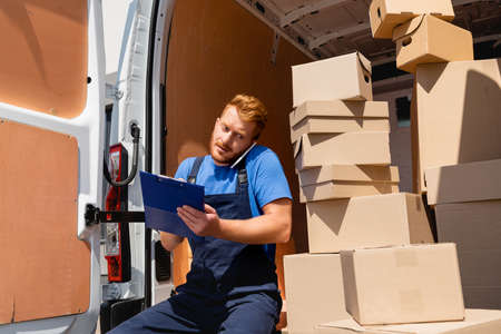 Loader in uniform holding clipboard while talking on smartphone near packages in truck Stockfoto