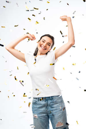 excited woman in white t-shirt with hands above head near confetti on white