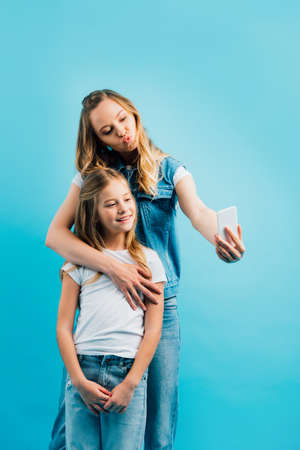 young woman pouting lips while taking selfie on smartphone with daughter wearing white t-shirt and jeans isolated on blue Stock Photo
