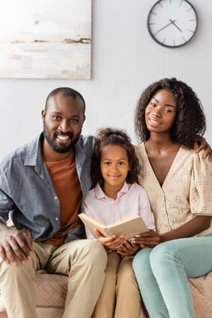 young african american parents and child with book looking at camera while sitting at home Stock fotó