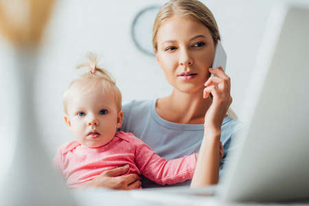 Selective focus of focused woman talking on smartphone and holding daughter at home