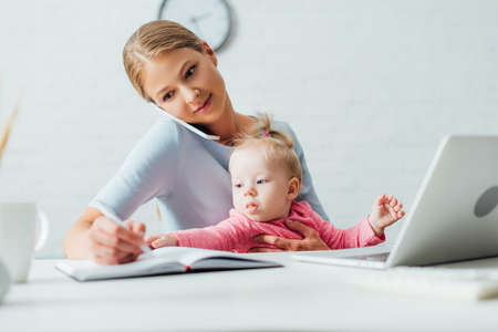 Selective focus of infant girl sitting near mother talking on smartphone and writing on notebook at home Stock Photo