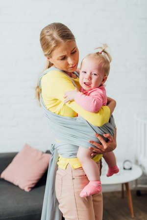 Woman holding crying infant daughter in baby sling at home