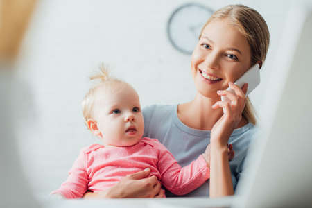 Selective focus of freelancer talking on smartphone and holding kid at home
