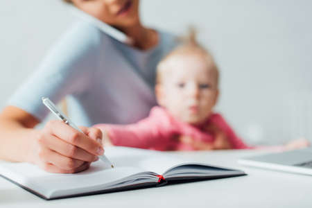 Selective focus of woman writing on notebook and talking on smartphone near child at home Stock Photo