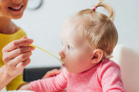Selective focus of woman feeding daughter with baby food at home