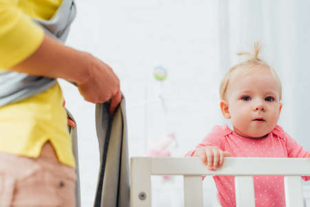 Selective focus of infant girl in crib looking at camera near mother in baby sling Stockfoto
