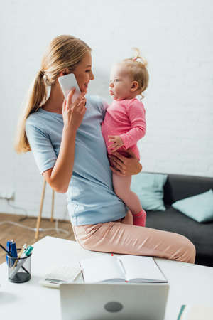 Selective focus of mother looking at baby girl while talking on smartphone near stationery and laptop on table