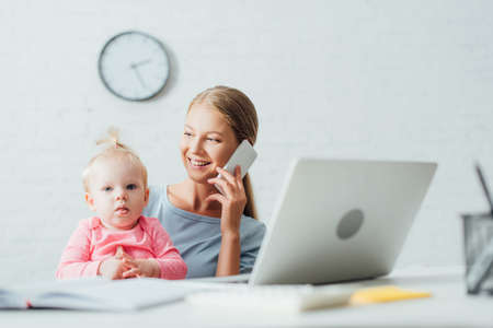 Selective focus of woman talking on smartphone while working near baby daughter at home