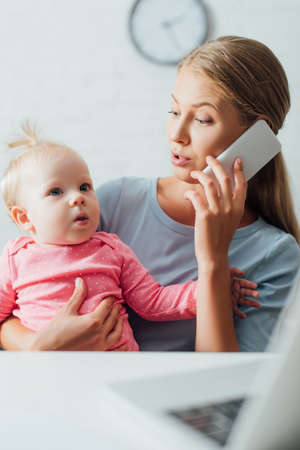 Selective focus of mother holding baby girl and talking on smartphone while working at home Stock Photo