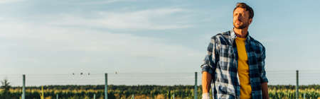 website header of rancher in plaid shirt looking away while standing in field on farm