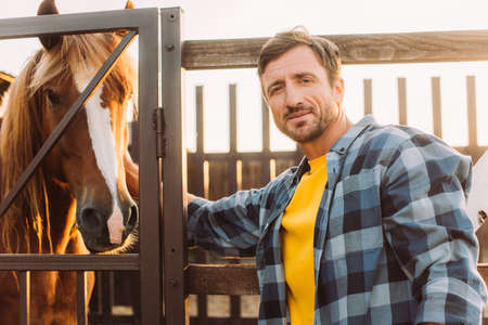 rancher in checkered shirt touching horse in corral and looking at camera