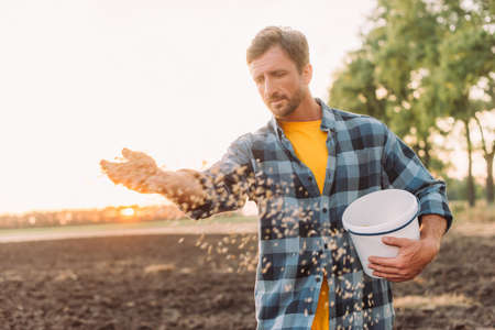 selective focus of farmer in plaid shirt sowing seeds on plowed field Foto de archivo