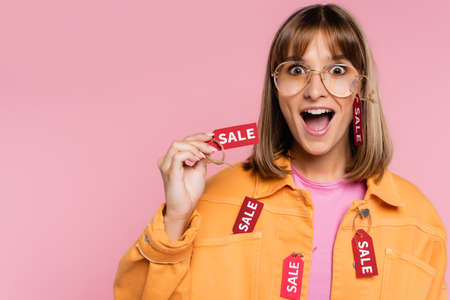 Shocked woman in sunglasses and yellow jacket holding price tag with sale word isolated on pink