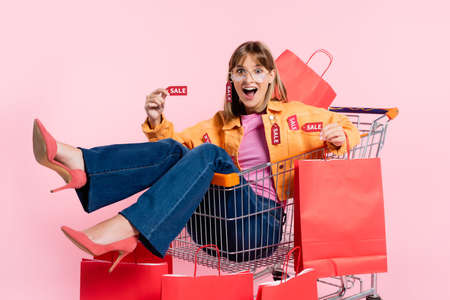 Excited woman in heels and sunglasses showing price tag and shopping bag in cart on pink background