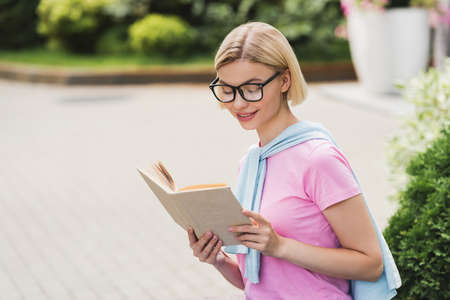 young blonde student in glasses reading book outside