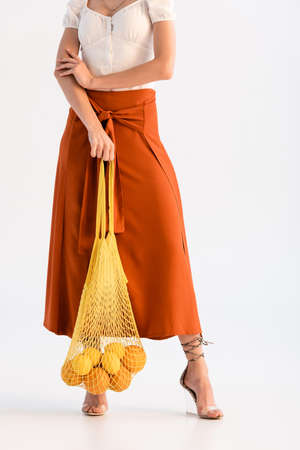 cropped view of fashionable woman posing with citrus fruits in string bag isolated on white