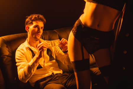 selective focus of man holding dollar banknote and looking at seductive woman on black