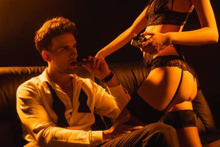 seductive woman holding lighter near man with cigar on black