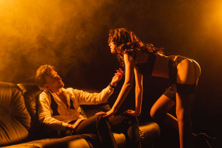 seductive woman in underwear looking at passionate man in suit on black with smoke