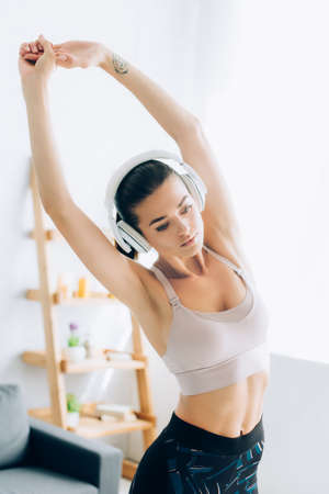 Young sportswoman listening music in headphones while training at home
