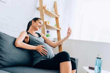 Pregnant sportswoman taking selfie with smartphone near sports bottle