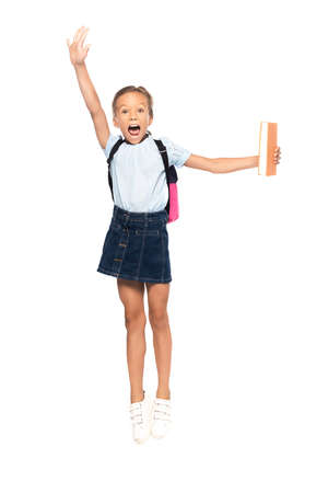 schoolgirl in glasses jumping and screaming while holding book isolated on white