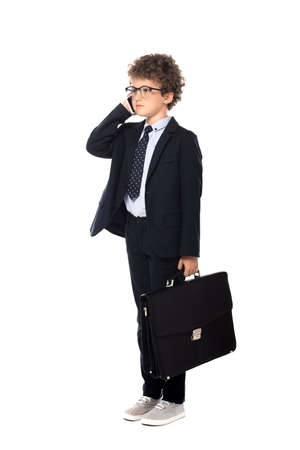 curly boy in suit and glasses holding briefcase while talking on smartphone isolated on white