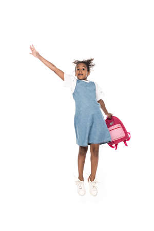 african american schoolgirl holding backpack and jumping with raised hand isolated on white