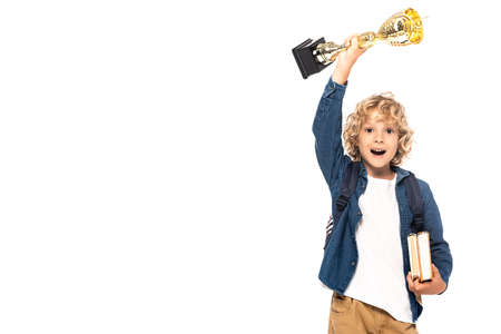 excited blonde schoolboy holding golden trophy and books isolated on white