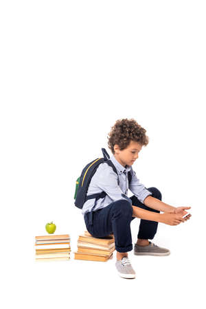 curly schoolboy with backpack sitting on books near apple and using smartphone isolated on white