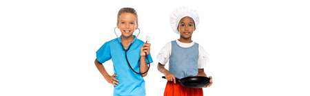 panoramic concept of multicultural kids in costumes of different professions holding frying pan and stethoscope isolated on white