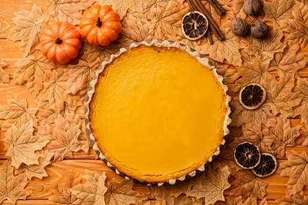 top view of pumpkin pie with autumnal decoration on wooden background Stock Photo