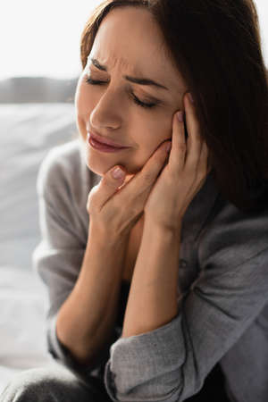 brunette woman with closed eyes touching face while suffering from toothache at home