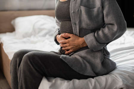 cropped view of woman suffering from stomach ache in bedroom