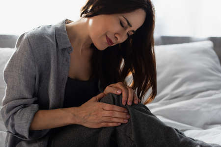 brunette woman suffering from pain in knee while sitting on bed at home