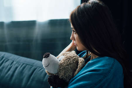 depressed brunette woman holding teddy bear while looking away