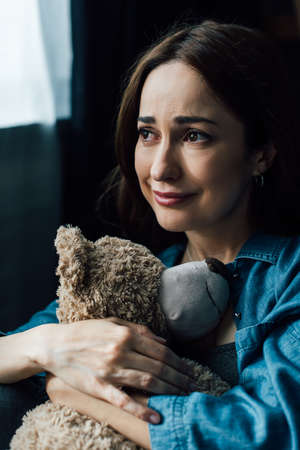 upset brunette woman holding teddy bear and looking away