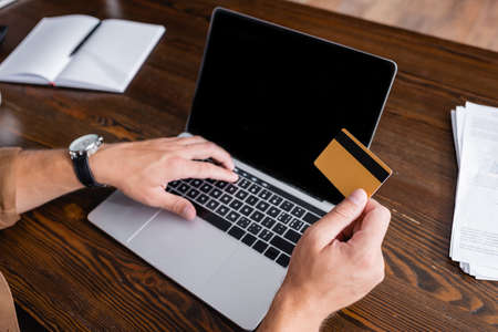 Cropped view of businessman holding credit card and using laptop near papers in office