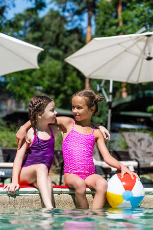 girls in swimsuits sitting at poolside with legs in water, embracing and looking at each other