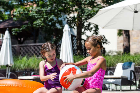 girl in swimsuit holding inflatable ball near friend and swim ring