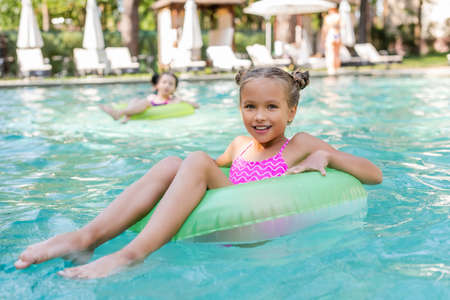 girl looking at camera while floating in pool on swim ring
