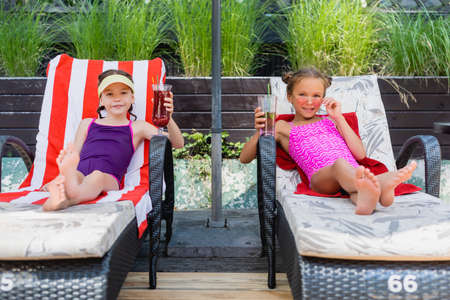 girls in swimsuits looking at camera while sitting in sunbeds with refreshing cocktails