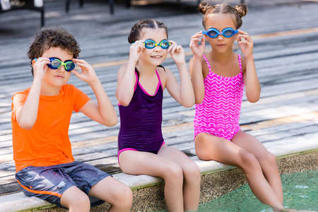 girls in swimsuits and boy in t-shirt touching swim goggles while sitting on pool deck Stock Photo
