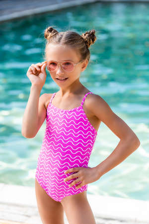 child in swimsuit touching sunglasses while posing with hand on hip near pool