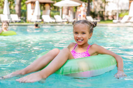 child looking at camera while floating in pool on inflatable ring