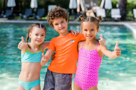 curly boy in t-shirt and girls in swimsuits showing thumbs up near pool