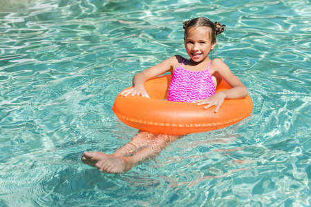 girl looking at camera while floating on inflatable ring in swimming pool