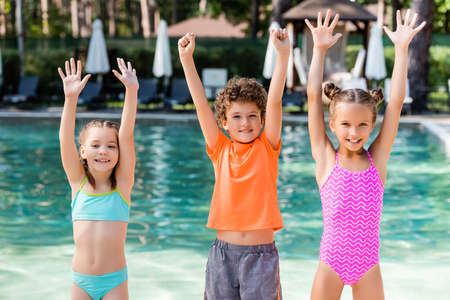 girls in swimsuits and boy in t-shirt standing with hands in air near pool