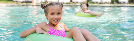 horizontal image of girl looking at camera while floating in pool on swim ring